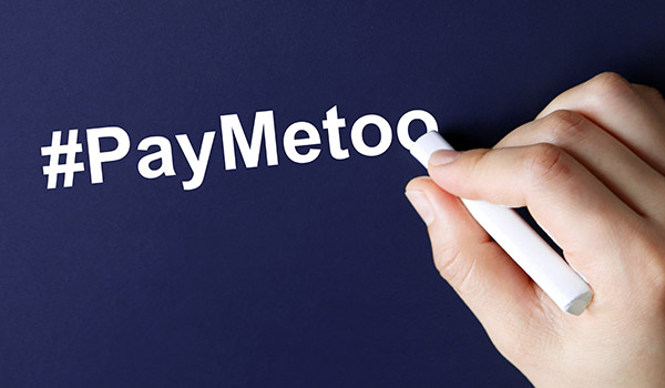 The hand writing text #PayMeToo in white chalk. A campaign to close the gender pay gap.
